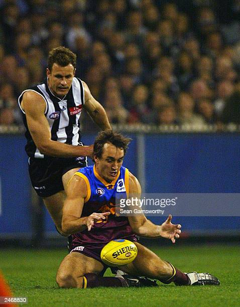 Daniel Bradshaw for Brisbane and James Clement for Collingwood contest the ball during the AFL second qualifying final between the Collingwood...