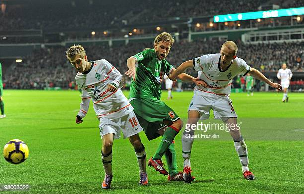 Daniel Brinkmann of Augsburg is challenged by Marko Marin and Petri Pasanen of Bremen during the DFB semi final match between SV Werder Bremen and FC...
