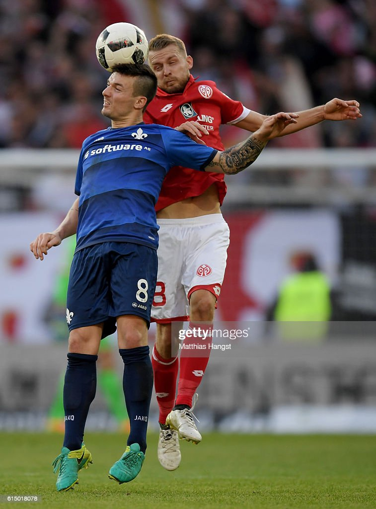 Daniel Brosinski (L) of Mainz and Jerome Gondorf (R) of Darmstadt head for the ball during the Bundesliga match between 1. FSV Mainz 05 and SV Darmstadt 98 at Opel Arena on October 16, 2016 in Mainz, Germany.