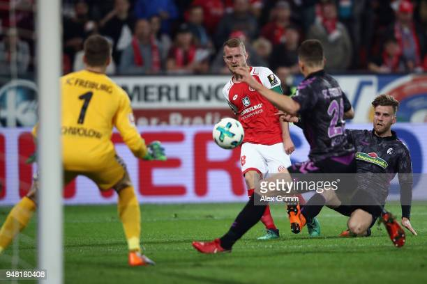 Daniel Brosinski of Mainz passes the ball past MarcOliver Kempf and goalkeeper Alexander Schwolow of Freiburg before referee Guido Winkmann calls a...