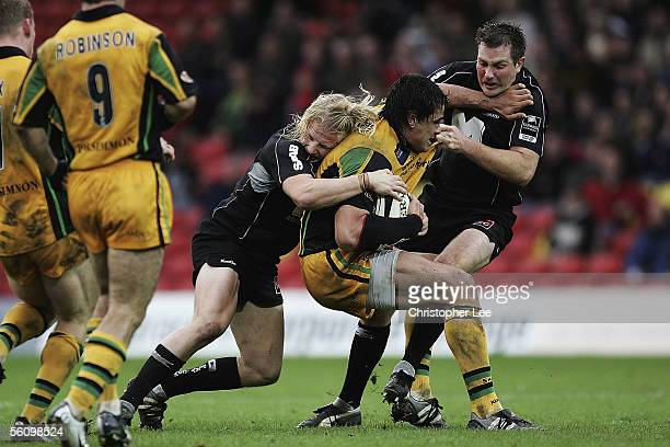 Daniel Browne of Northampton is stopped by David Seymour and Glen Jackson of Saracens during the Guinness Premiership match between Saracens and...