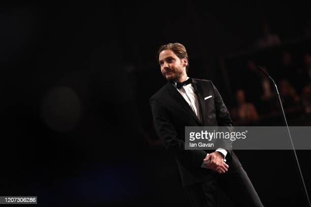 Daniel Bruehl watches the screen as the nominees are shown for Laureus Sportsman of the Year on stage during the 2020 Laureus World Sports Awards at...