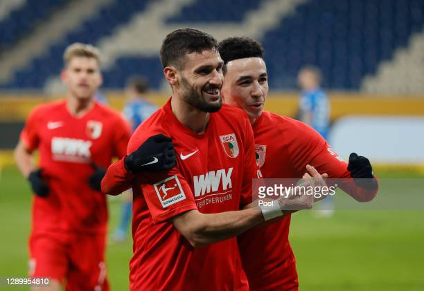 Daniel Caligiuri of Augsburg celebrates his team's first goal with teammate Ruben Vargas during the Bundesliga match between TSG Hoffenheim and FC...