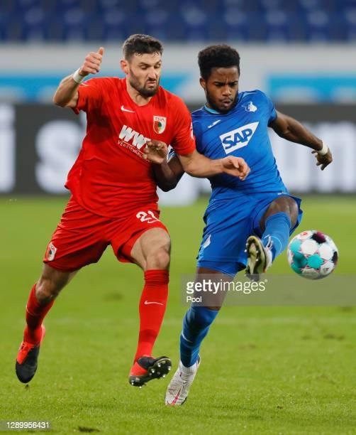 Daniel Caligiuri of Augsburg is challenged by Ryan Sessegnon of Hoffenheim during the Bundesliga match between TSG Hoffenheim and FC Augsburg at...