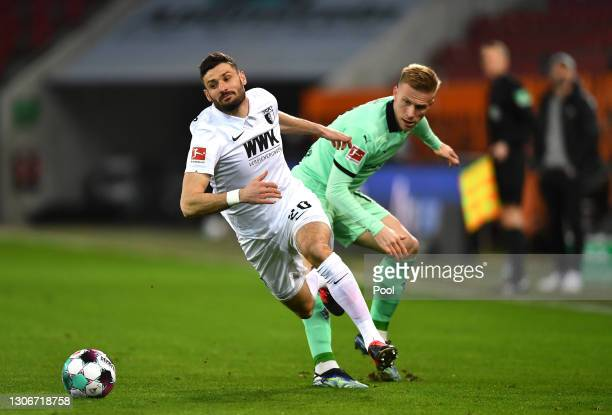 Daniel Caligiuri of Augsburg is fouled by Oscar Wendt of Borussia Moenchengladbach during the Bundesliga match between FC Augsburg and Borussia...