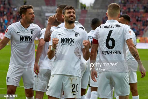 Daniel Caligiuri of FC Augsburg celebrates after scoring his team's second goal with teammates during the 1. Bundesliga match between FC Augsburg and...