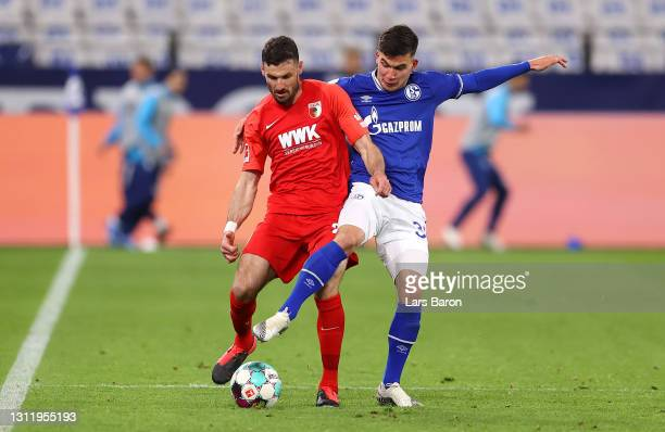 Daniel Caligiuri of FC Augsburg is challenged by Mehmet-Can Aydin of FC Schalke 04 during the Bundesliga match between FC Schalke 04 and FC Augsburg...