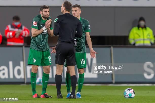 Daniel Caligiuri of FC Augsburg, referee Bastian Dankert and Laszlo Benes of FC Augsburg gestures during the Bundesliga match between Sport-Club...