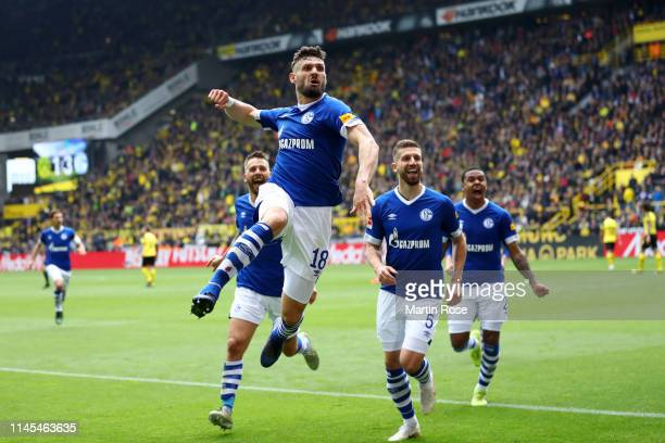 Daniel Caligiuri of FC Schalke 04 celebrates after scoring his team's third goal with team mates during the Bundesliga match between Borussia...