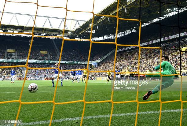 Daniel Caligiuri of FC Schalke 04 scores his team's first goal from a penalty past Roman Buerki of Borussia Dortmund during the Bundesliga match...