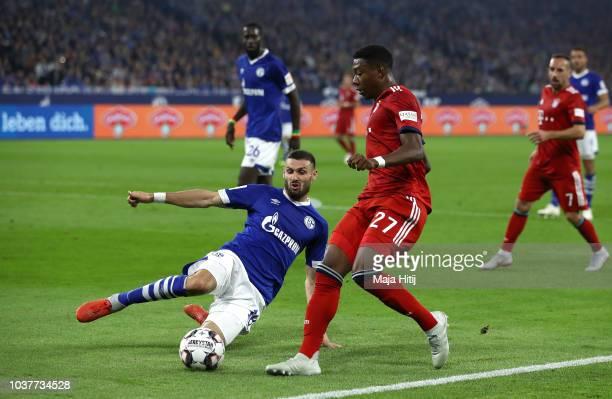 Daniel Caligiuri of FC Schalke 04 tackles David Alaba of Bayern Munich during the Bundesliga match between FC Schalke 04 and FC Bayern Muenchen at...