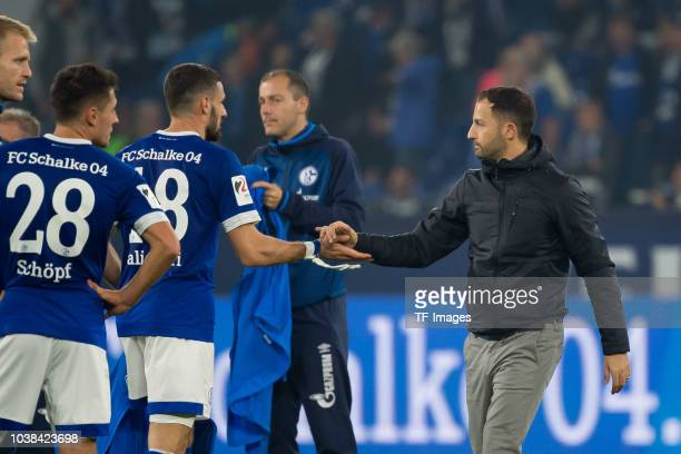 Daniel Caligiuri of FC Schalke and Head coach Domenico Tedesco of FC Schalke slap hands during the Bundesliga match between FC Schalke 04 and FC...