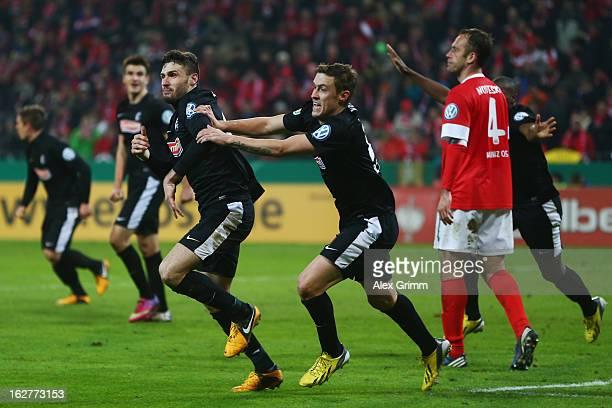 Daniel Caligiuri of Freiburg celebrates his team's third goal with team mate Max Kruse as Nikolce Noveski of Mainz reacts during the DFB Cup Quarter...