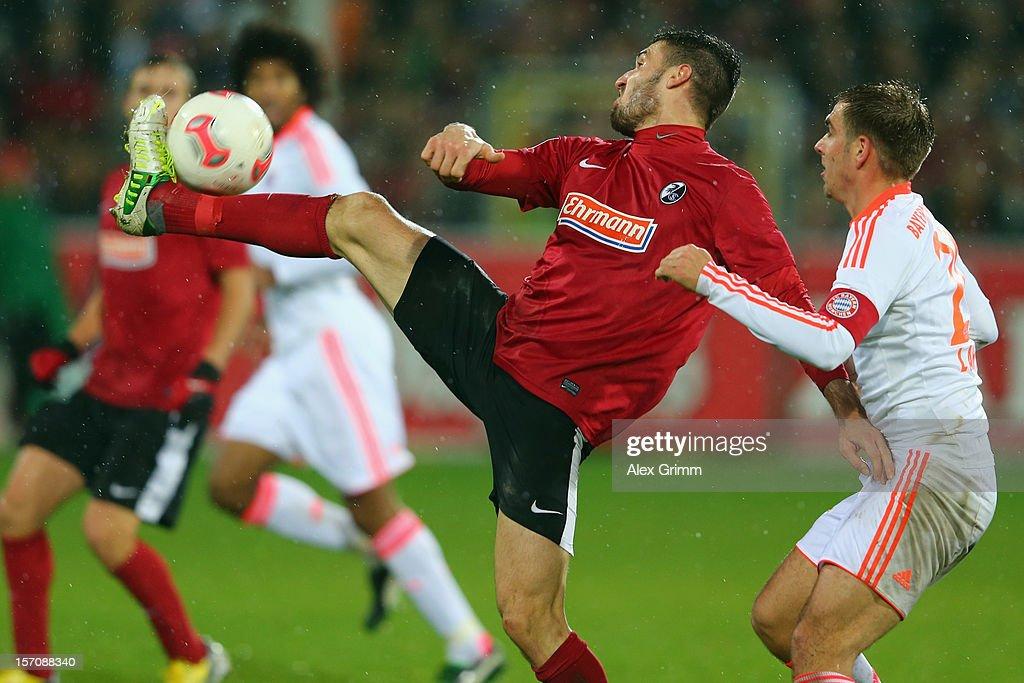 Daniel Caligiuri (L) of Freiburg is challenged by Philipp Lahm of Muenchen during the Bundesliga match between SC Freiburg and FC Bayern Muenchen at MAGE SOLAR Stadium on November 28, 2012 in Freiburg im Breisgau, Germany.