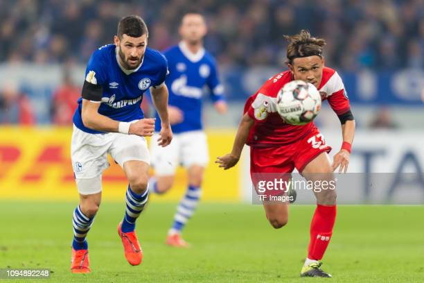 Daniel Caligiuri of Schalke 04 and Takashi Usami of Fortuna Duesseldorf battle for the ball during the DFB Pokal Cup match between FC Schalke 04 and...
