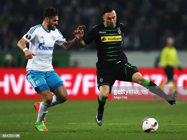 Daniel Caligiuri of Schalke 04 challenges Josip Drmic of Borussia Moenchengladbach during the UEFA Europa League Round of 16 second leg match between...