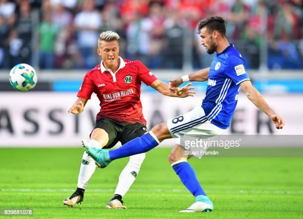 Daniel Caligiuri of Schalke 04 is challenged by Matthias Ostrzolek of Hannover 96 during the Bundesliga match between Hannover 96 and FC Schalke 04...