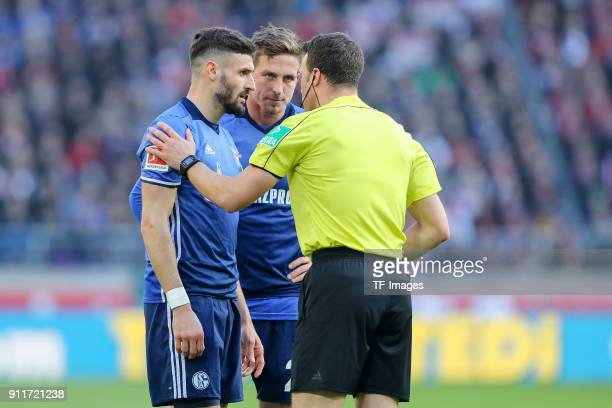 Daniel Caligiuri of Schalke and Bastian Oczipka of Schalke speaks with referee Felix Zwayer during the Bundesliga match between VfB Stuttgart and FC...