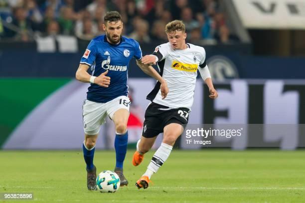 Daniel Caligiuri of Schalke and Mickael Cuisance of Moenchengladbach battle for the ball during the Bundesliga match between FC Schalke 04 and...