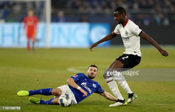 Daniel Caligiuri of Schalke challenges Evan N'Dicka of Frankfurt during the Bundesliga match between FC Schalke 04 and Eintracht Frankfurt at...