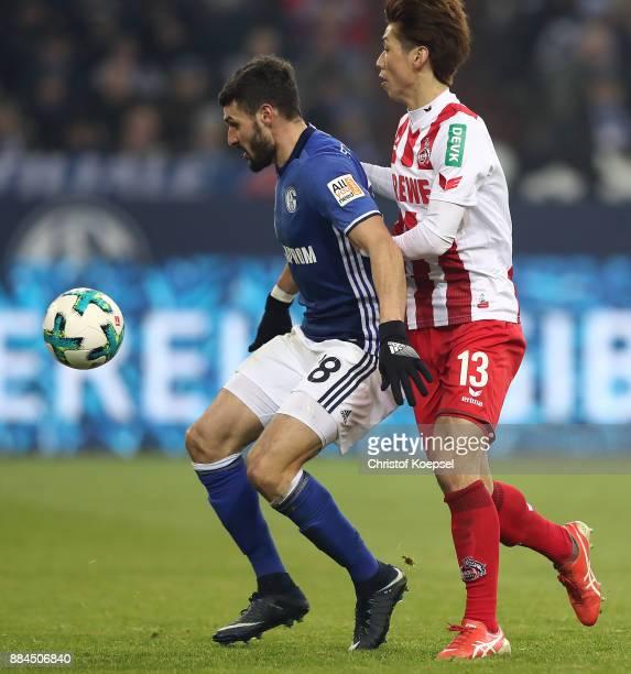 Daniel Caligiuri of Schalke fights for the ball with Yuya Osako of Koeln during the Bundesliga match between FC Schalke 04 and 1 FC Koeln at...