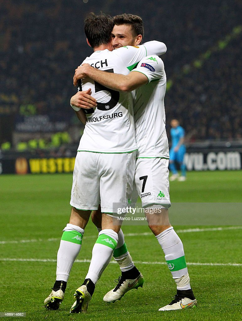 Daniel Caligiuri (R) of VfL Wolfsburg celebrates with his team-mate Christian Trasch (L) after scoring the opening goal during the UEFA Europa League Round of 16 match between FC Internazionale Milano and VfL Wolfsburg at Stadio Giuseppe Meazza on March 19, 2015 in Milan, Italy.