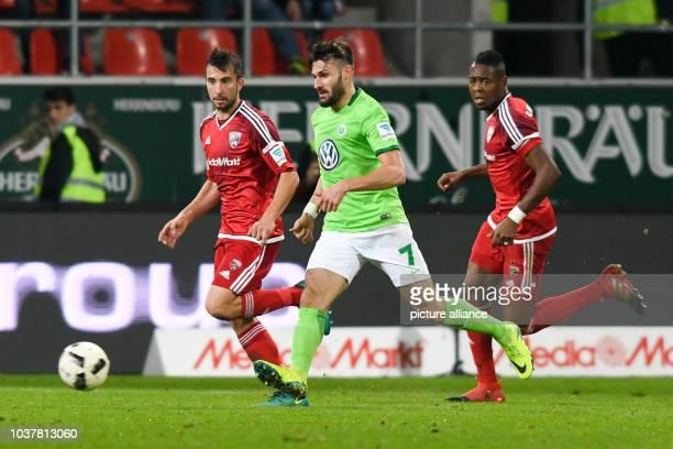 Daniel Caligiuri of Wolfsburg in action beside Roger de Oliveira Bernardo and Markus Suttner of Ingolstadt during the German Bundesliga soccer match...