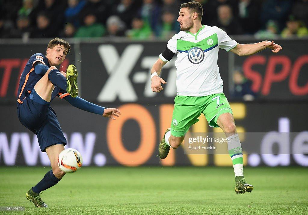 Daniel Caligiuri of Wolfsburg is challenged by Luca-Milan Zander of Bremen during the Bundesliga match between VfL Wolfsburg and Werder Bremen at Volkswagen Arena on November 21, 2015 in Wolfsburg, Germany.