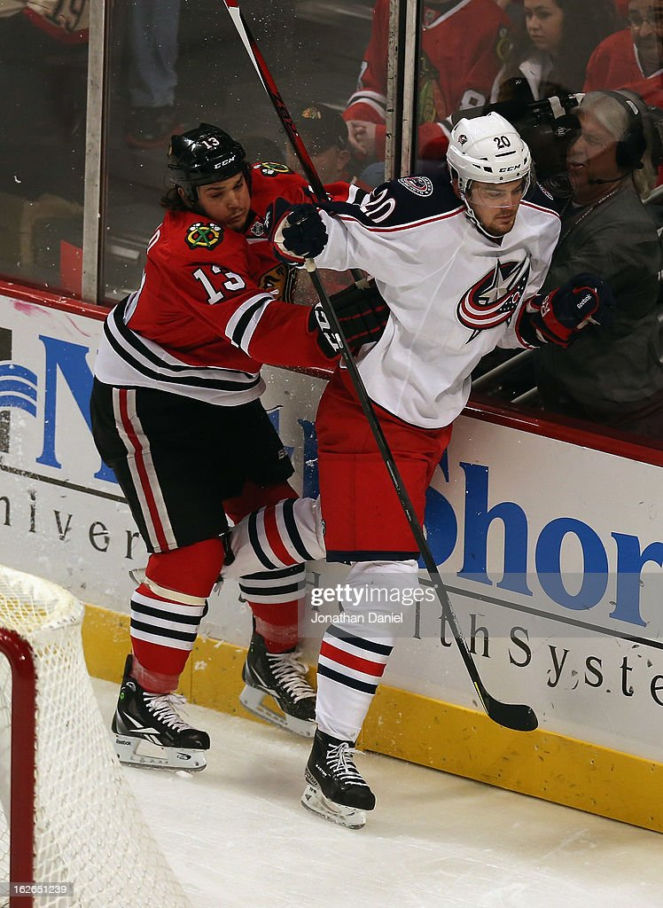 Daniel Carcillo #13 of the Chicago Blackhawks checks Tim Erixon #20 of the Columbus Blue Jackets at the United Center on February 24, 2013 in Chicago, Illinois. The Blackhawks defeated the Blue Jackets 1-0.