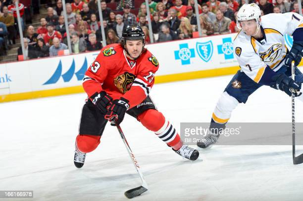Daniel Carcillo of the Chicago Blackhawks grabs the puck as Jonathon Blum of the Nashville Predators watches from the side during the NHL game on...