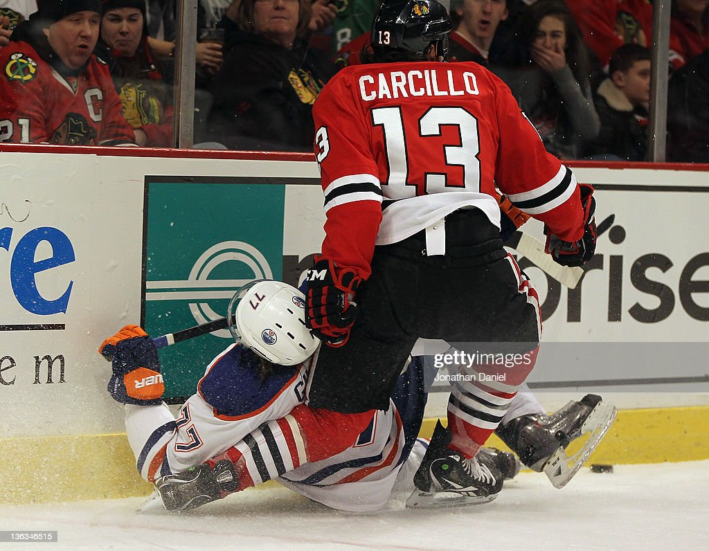 Daniel Carcillo #13 of the Chicago Blackhawks injures his knee after boarding Tom Gilbert #77 of the Edmonton Oilers at the United Center on January 2, 2012 in Chicago, Illinois.