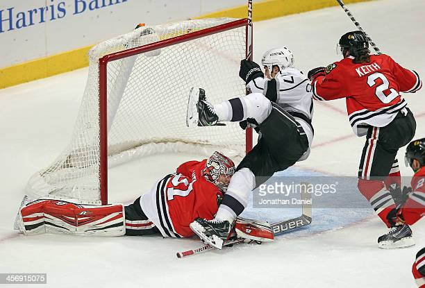 Daniel Carcillo of the Los Angeles Kings falls over Antti Raanta of the Chicago Blackhawks as Duncan Keith chases the puck at the United Center on...