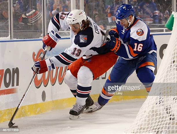 Daniel Carcillo of the New York Rangers skates the puck past Peter Regin of the New York Islanders during the 2014 Coors Light NHL Stadium Series at...