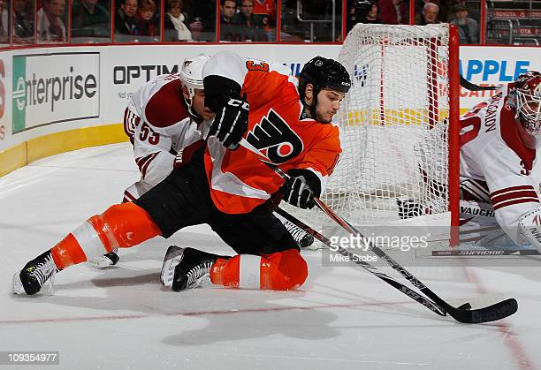 Daniel Carcillo of the Philadelphia Flyers falls to the ice playing the puck against Derek Morris of the Phoenix Coyotes on February 22 2011 at the...