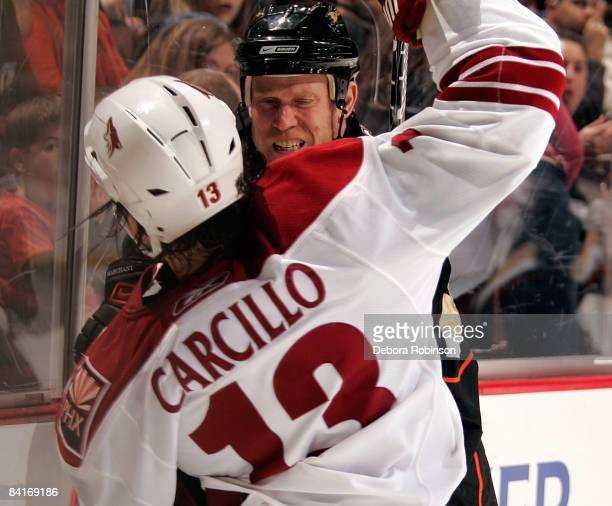 Daniel Carcillo of the Phoenix Coyotes takes a hit from Todd Marchant of the Anaheim Ducks during the game on January 4 2009 at Honda Center in...