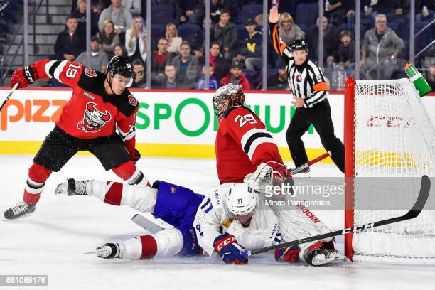 Daniel Carr of the Laval Rocket falls as he slides the puck underneath goaltender Mackenzie Blackwood of the Binghamton Devils during the AHL game at...