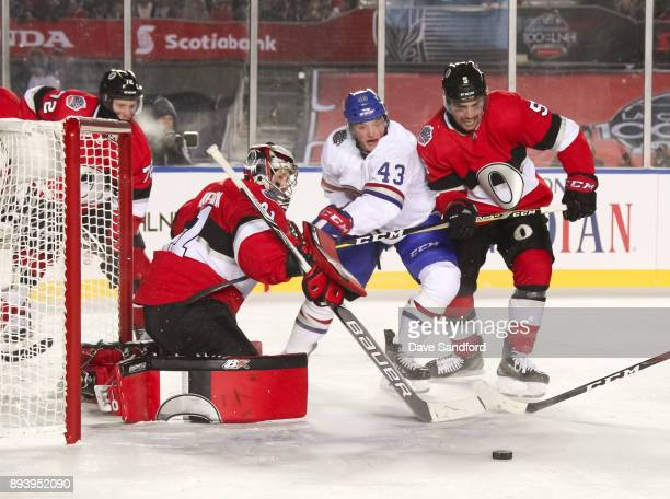 Daniel Carr of the Montreal Canadiens battles for a loose puck with Cody Ceci of the Ottawa Senators in front of teammate Craig Anderson during the...