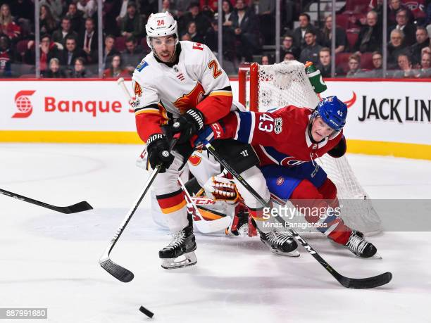 Daniel Carr of the Montreal Canadiens challenges Travis Hamonic of the Calgary Flames during the NHL game at the Bell Centre on December 7 2017 in...