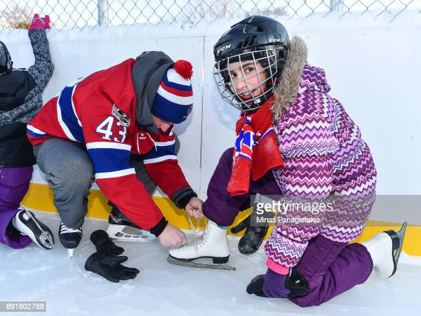 Daniel Carr of the Montreal Canadiens helps a young girl tie her skates during the official inauguration of the Bleu Blanc Bouge rink by the Montreal...