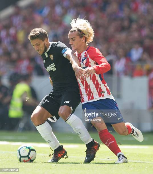 Daniel Carrico of Sevilla FC fends off Antoine Greizmann of Club Atletico de Madrid during the La Liga match between Atletico Madrid and Sevilla at...