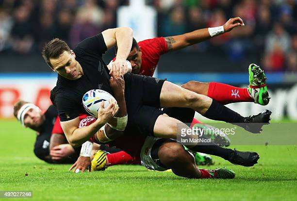 Daniel Carter of New Zealand is tackled by Halani Aulika of Tonga during the New Zealand and Tonga Group C Rugby World Cup match at St James Park on...