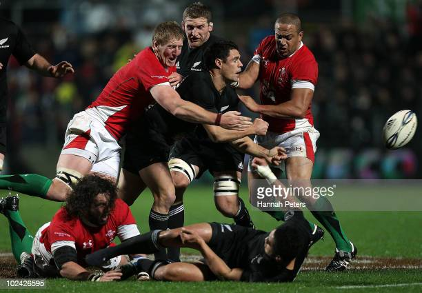 Daniel Carter of New Zealand offloads the ball during the test match between the New Zealand All Blacks and Wales at Waikato Stadium on June 26 2010...