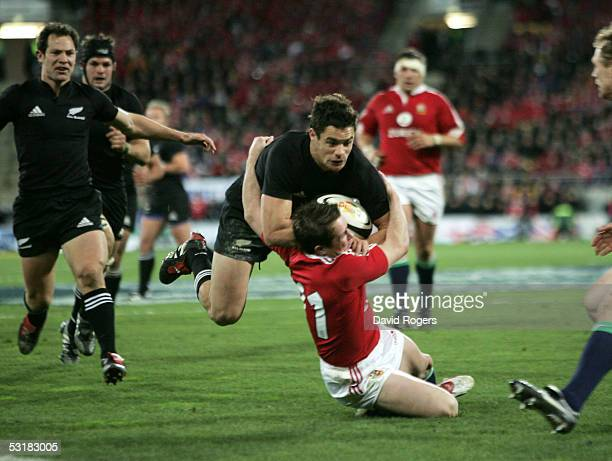 Daniel Carter the All Black standoff is tackled by Shane Williams during the second test match between The New Zealand All Blacks and the British and...