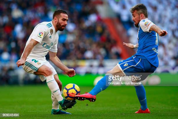 Daniel Carvajal of Real Madrid CF competes for the ball with Luisinho Correia Deportivo La Coruna during the La Liga match between Real Madrid CF and...