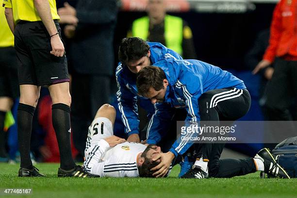Daniel Carvajal of Real Madrid CF grimaces in pain laying on the ground assited by Real Madrid technical staff before leving the pitch during the La...