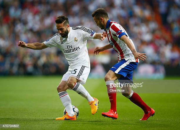 Daniel Carvajal of Real Madrid CF holds off Saul Niguez of Atletico Madrid during the UEFA Champions League quarterfinal second leg match between...