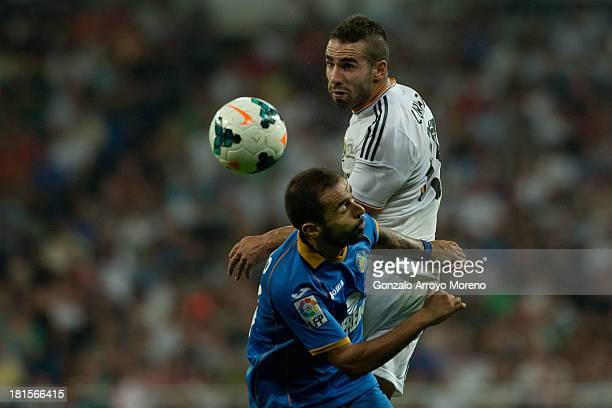 Daniel Carvajal of Real Madrid CF wins the header before Diego Castro of Getafe CF during the La Liga match between Real Madrid CF and Getafe CF at...