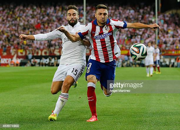 Daniel Carvajal of Real Madrid competes for the ball with Guilherme Siqueira of Atletico de Madrid during the Supercopa second leg match between...