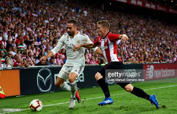 Daniel Carvajal of Real Madrid competes for the ball with Iker Muniain of Athletic Club during the La Liga match between Athletic Club Bilbao and...