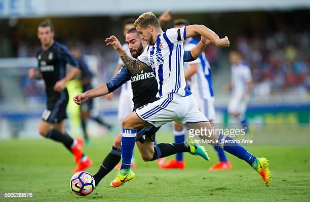 Daniel Carvajal of Real Madrid duels for the ball with Inigo Martinez of Real Sociedad during the La Liga match between Real Sociedad de Futbol and...